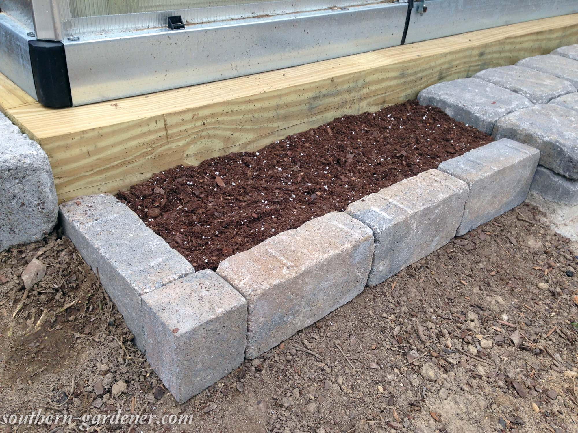 narrow flower bed with brick pavers